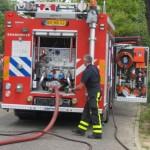 brandweerman bezig achter brabdweer auto met slang 2011